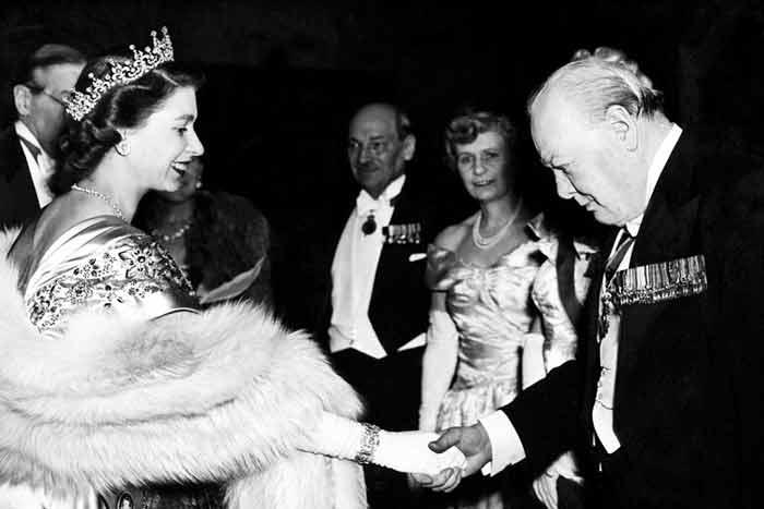 De oude staatsman Winston Churchill buigt het hoofd wanneer hij koning Elizabeth een hand geeft. de foto is gemaakt in 1953